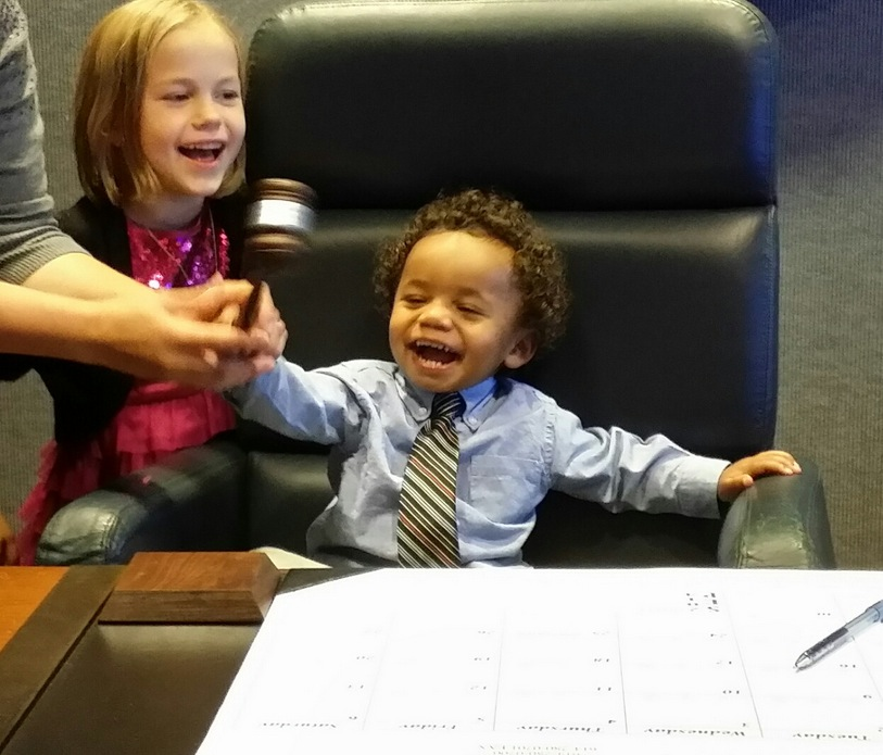 Our son and his big sister ringing in his official adoption and the end of his time in foster care