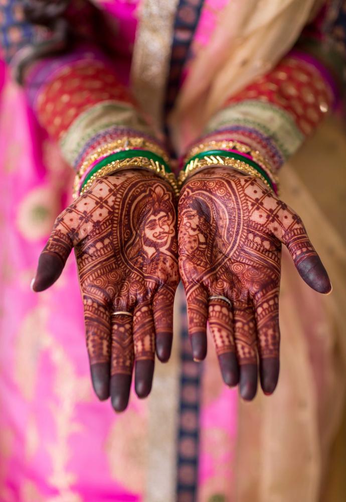 Bridal wearing wedding bangles and showing mehndi design